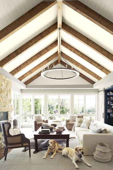 A naturally lit living room with neutral accents and high wood beamed ceiling