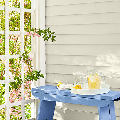 Off-white exterior siding with a blue bench holding a pitcher of lemonade.