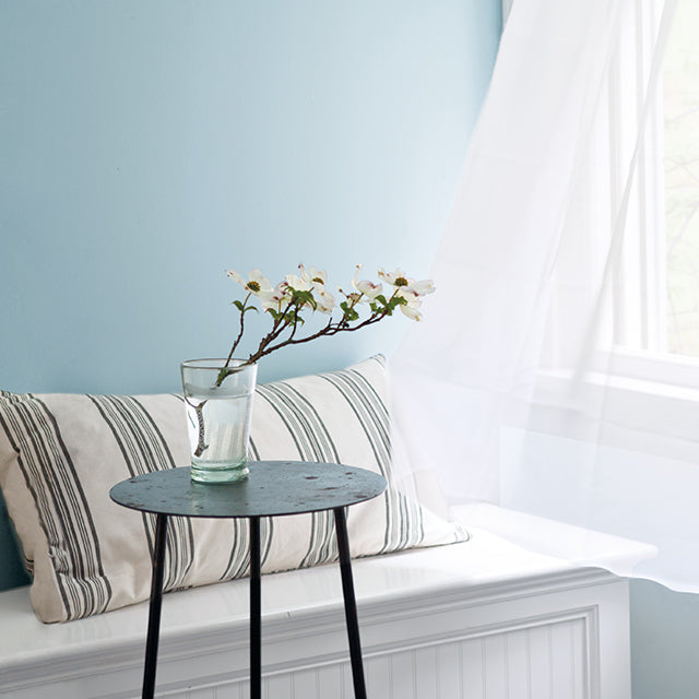 Light blue-painted walls with an open window and shear white curtains blowing in the wind featuring a bench with a striped pillow and black side table.