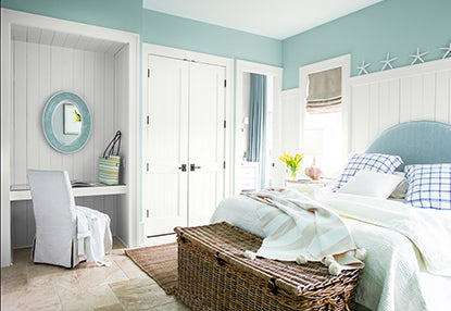 Light blue-painted bedroom walls with a white built-in desk, a large bed with light and dark blue pillows and comforter.
