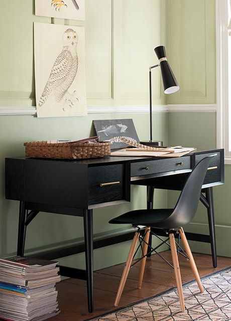 A monochromatic home office featuring two-toned green walls with two photos hanging above a black desk and chair.