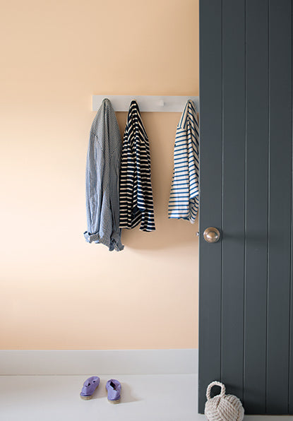 Peach-painted walls with three jackets hanging from a mounted rack with a black door propped open with a door weight.