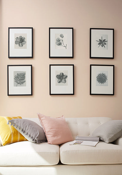 Dusty pink-painted walls with six picture frames hung above a white couch with yellow, pink, and gray throw pillows.