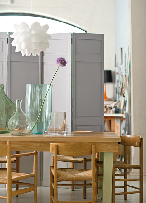 A dining area with wood table, four chairs, and a greige partition.