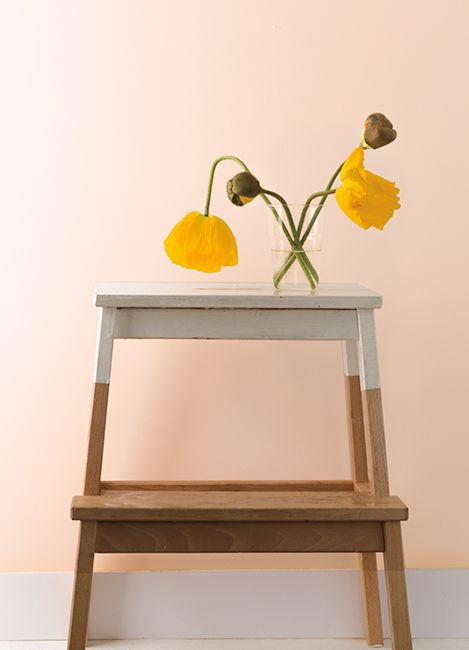 Pale peach walls with two yellow flowers in a vase set on top of a two-toned step stool.