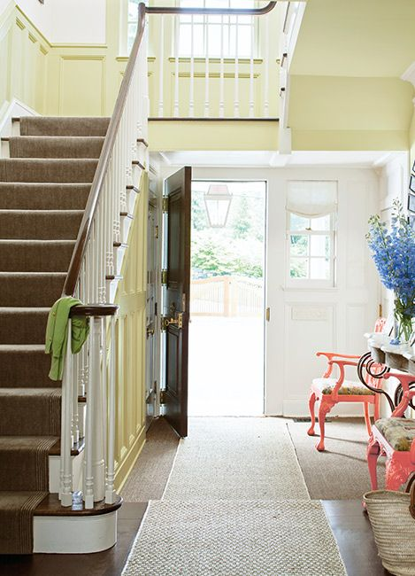 A house entryway with medium yellow walls, wood floors, and two pink chairs on either side of a console table with a mirror hung above.