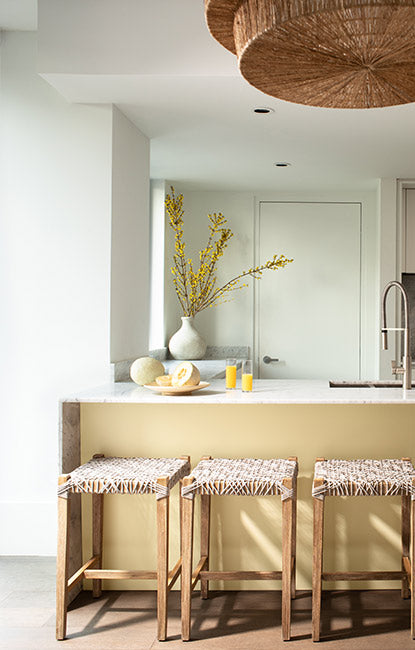 Small kitchen with white-painted walls, a yellow kitchen island and three rattan barstools.