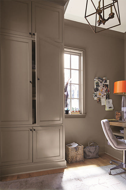 A taupe-painted home office with cupboard, beige chair, wooden desk, note board, white ceiling, and abstract chandelier.