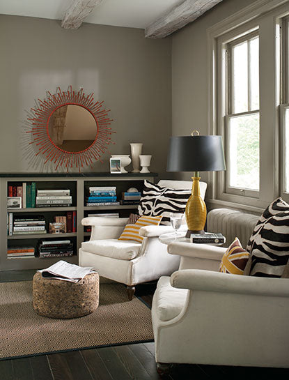 A cozy living room corner with two wing chairs and walls painted in Sparrow AF-720, a deep taupe color.