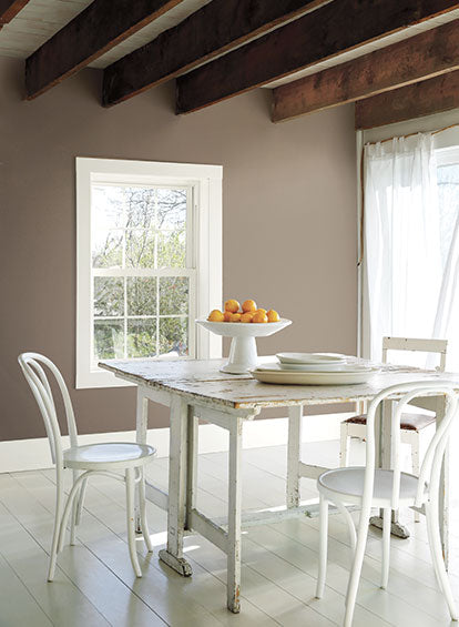A dining area with exposed ceiling beams and walls painted in Weimaraner AF-155.