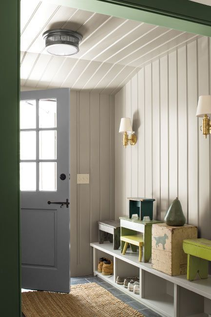 A white painted mudroom, with forest green trim and built in cubbies.