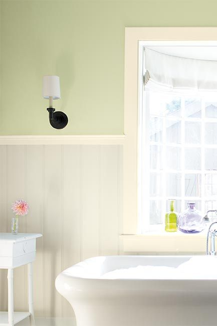 A light green-painted bathroom, detailed with white wainscoting and a stand alone tub.