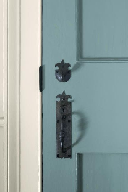 A light blue-painted paneled door with a traditional black handle.