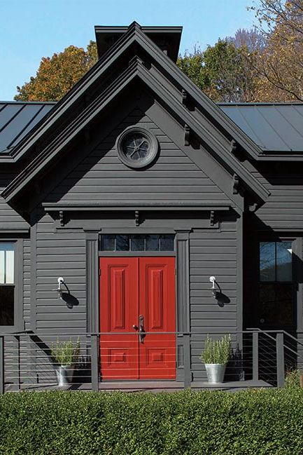 A charcoal gray-painted colonial home that pops with a front door in red.