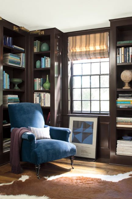 A deep blue-painted library with built in shelves, an animal hide rug, and dark blue velvet chair.