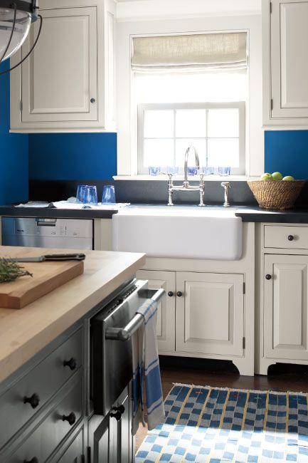 A blue-painted kitchen with white cabinets, a butcher block countertop island and white farmhouse sink.