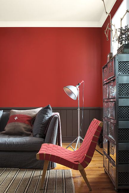 A red living room with brown wainscoting and a contemporary red woven chair.