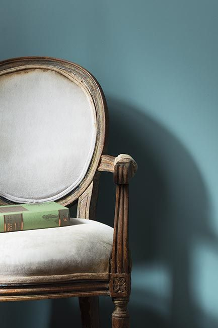 A pale blue-painted wall with a traditional round back chair.