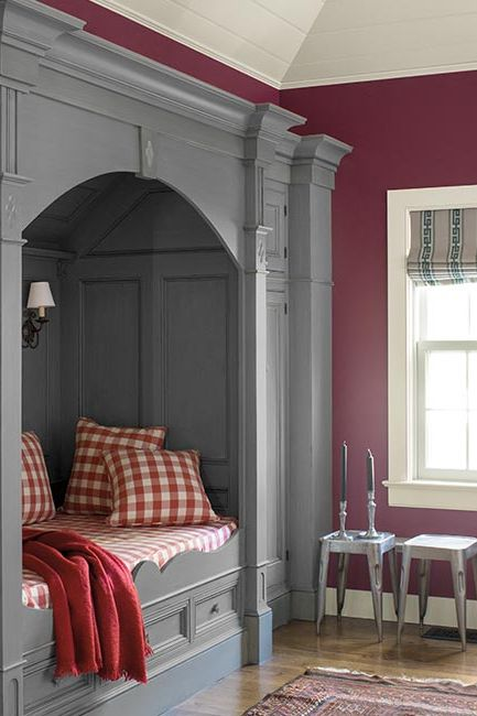 A crisp magenta room with a gray paneled & trim built in bed with red gingham bedding.