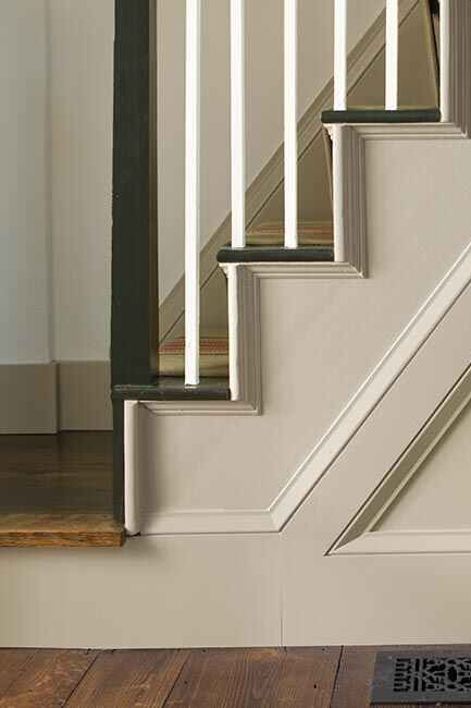 A sideview of white-painted stairs with white spindles and black handrail.