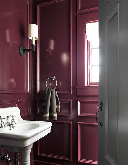 A bold plum-painted paneled bathroom featuring a white antique sink.