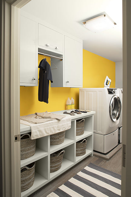Laundry room with white cabinets and a yellow wall painted in Sunshine 2021-30.