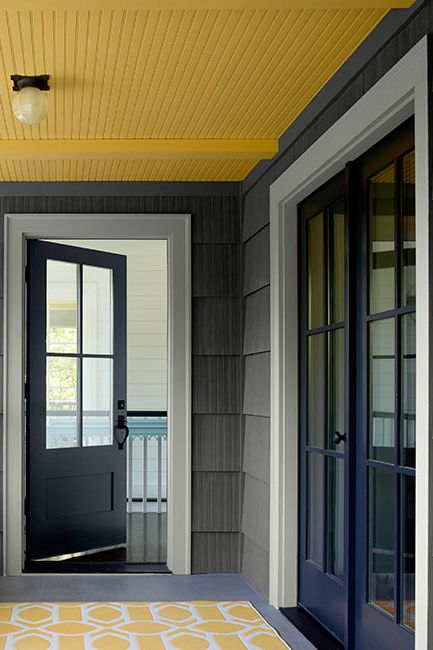 A covered porch area with a yellow ceiling painted in Marblehead Gold 2120-30.