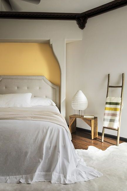 A neutral colored bedroom with a pale yellow recessed bed wall painted in York Harbor Yellow 2154-40.