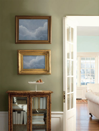 A light green-painted hallway opens to a neutral family room through a white door.