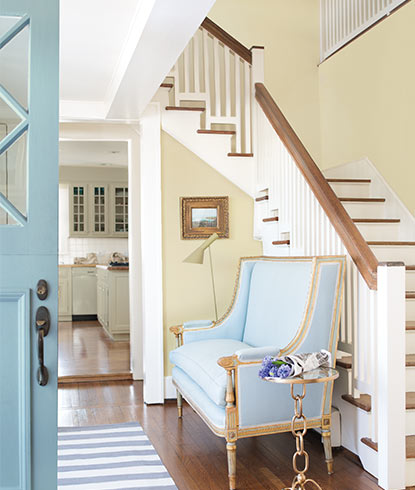 A bright entryway in neutral shades includes a staircase, blue chaise and light blue front door.