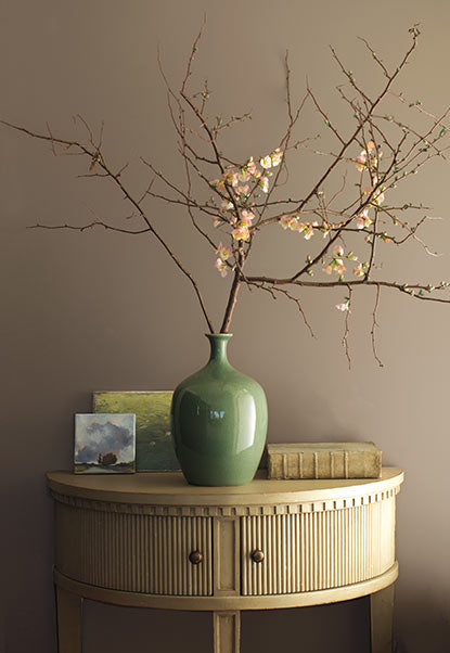 Minimalist floral arrangement in green vase against gray-brown wall.