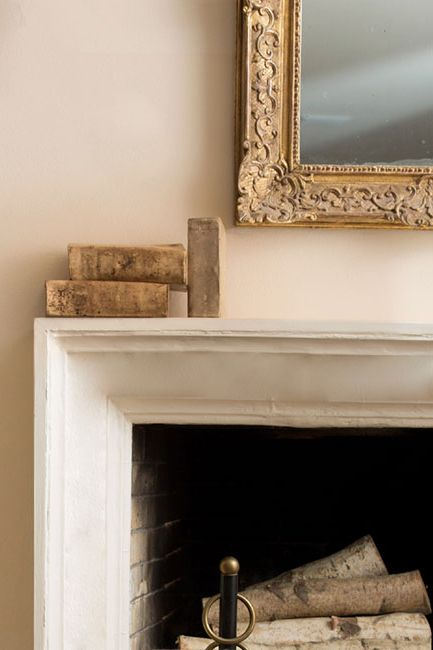 Fireplace mantle with vintage mirror and books