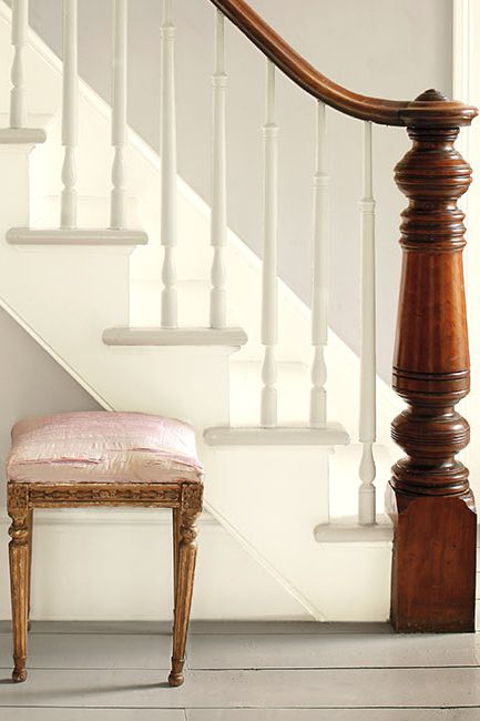 Gray walls accented by white stairs create an elegant entryway featuring three ornate stools.