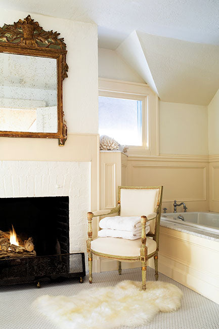 Luxurious master bathroom with fireplace and armchair