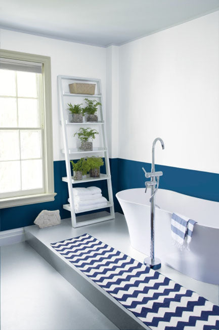 Navy blue and white bathroom with chevron rug and large bathtub