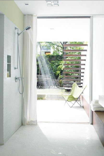 Open, airy shower with green accents and floor to ceiling windows