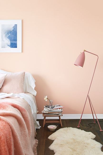 A dreamy bedroom with walls painted in Pleasant Pink 2094-60 and matching pink lamp and bedspread.