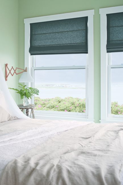 Green bedroom with window side bed.