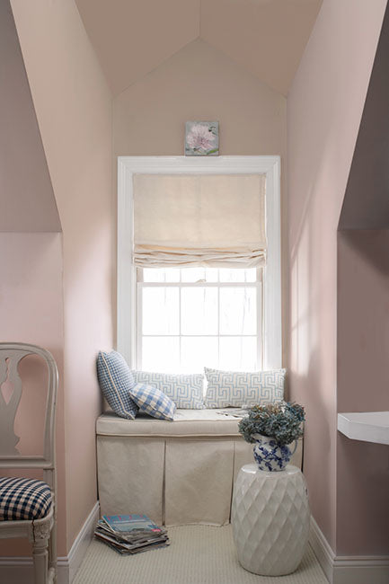 A window-seat area with pink walls and angled ceilings.