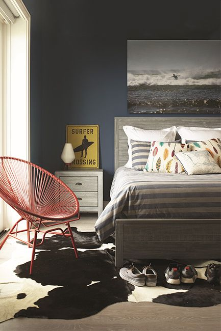 A dark rich blue bedroom with surfer-inspired décor.