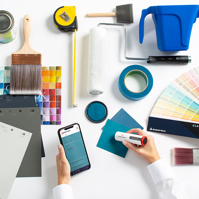 A professional evaluating different paint color swatches and tools to complete their color portfolio.