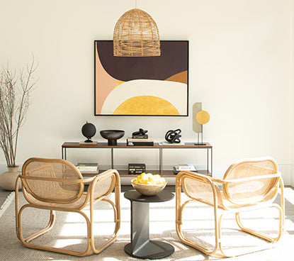 White walls with a long wall table, two rattan chairs and a black side table.
