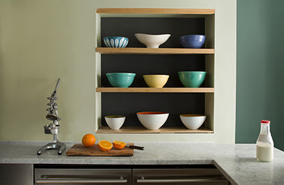 Monochromatic kitchen walls with shades of dark and light green including three inset shelves holding 9 bowls.