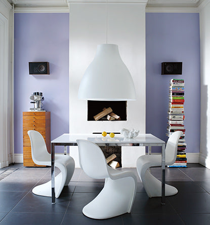 Light blue-magenta walls with a white fireplace featuring a modern dining room table and white chairs.