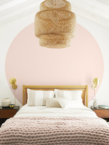 Bedroom with white walls and a large light pink circle behind white bed with pink throw blanket and a basket chandelier.