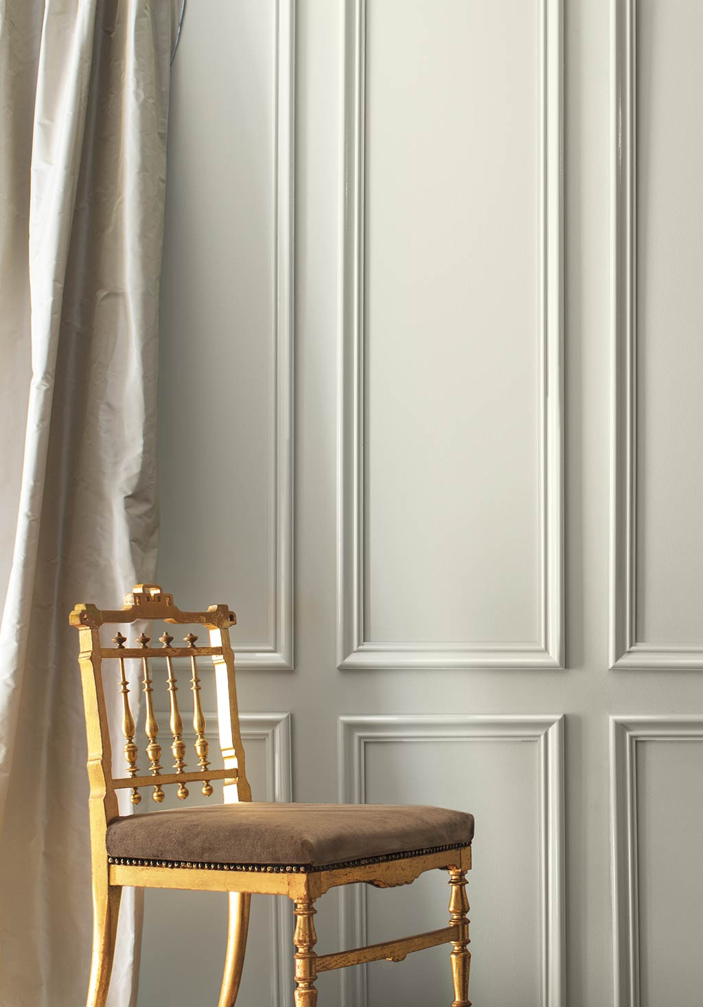 A gray-painted wall and cream-colored silk curtains frame a formal gold chair. Color of the Year 2019