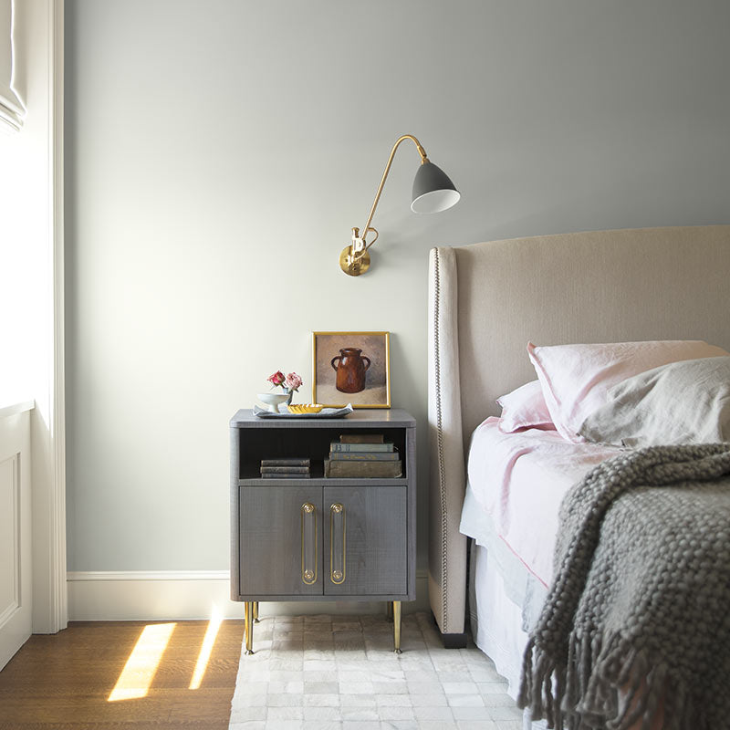 An airy bedroom with gray-painted walls and white trim features neutral bedding and metallic accents. Color of the Year 2019