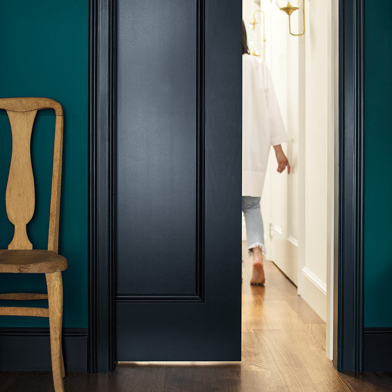 A deep blue-green-painted wall and navy-painted door opens to an off-white hallway. Color of the Year 2019