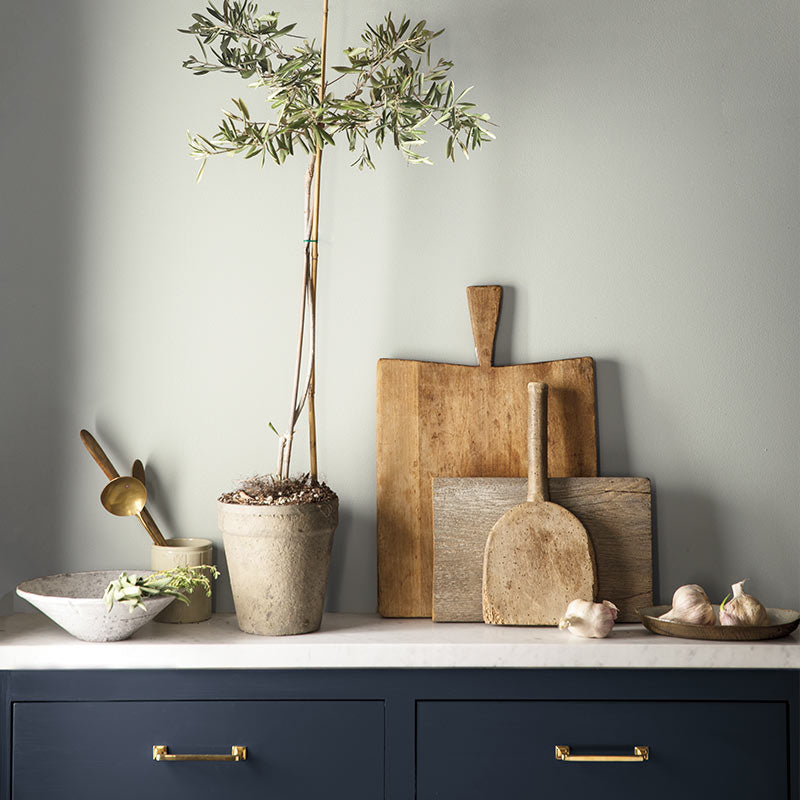 A navy-painted cabinet against a gray-painted wall features cutting boards and other kitchen items. Color of the Year 2019
