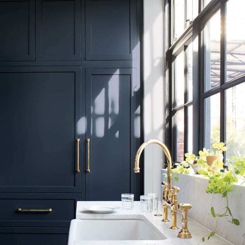 Navy-painted cabinets in a sleek kitchen with marble countertop, gold hardware and black trimmed windows. Color of the Year 2019